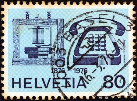 stempeln: SWITZERLAND - CIRCA 1976: A stamp printed in Switzerland issued for the telephone centenary shows telephones of 1876 and 1976, circa 1976.