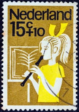 orange nassau: NETHERLANDS - CIRCA 1964: A stamp printed in the Netherlands from the Child Welfare issue shows a girl playing the recorder, circa 1964.  Editorial
