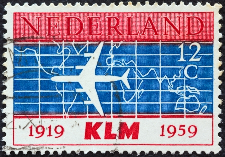 nederlan: NETHERLANDS - CIRCA 1959: A stamp printed in the Netherlands issued for the 40th anniversary of K.L.M. (Royal Dutch Airlines) shows silhouette of Douglas DC-8 Airliner and World Map, circa 1959.  Editorial