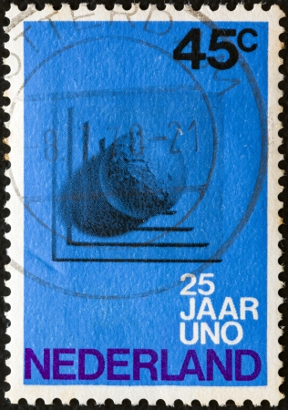 nederlan: NETHERLANDS - CIRCA 1970: A stamp printed in the Netherlands issued for the 25th anniversary of United Nations shows Globe on Plinth, circa 1970.