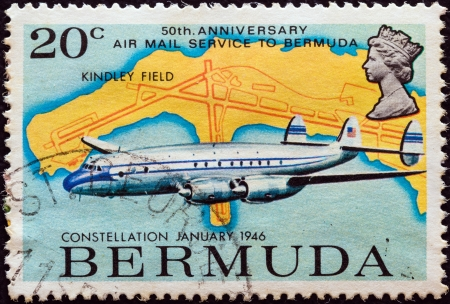 BERMUDA - CIRCA 1975: A stamp printed in Bermuda from the '50th anniversary of Air-mail service to Bermuda' issue shows Lockheed Constellation of 1946 and Kindley field airport map, circa 1975.