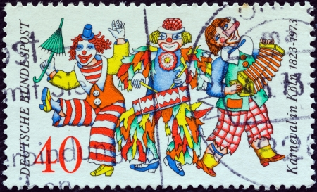 revellers: GERMANY - CIRCA 1972: A stamp printed in Germany issued for the 150th anniversary of Cologne Carnival shows three clowns, circa 1972.