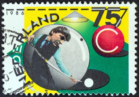 nederlan: NETHERLANDS - CIRCA 1986: A stamp printed in the Netherlands issued for the 75th Royal Dutch Billiards Association, Checkers Association shows Player in ball preparing to play, circa 1986.