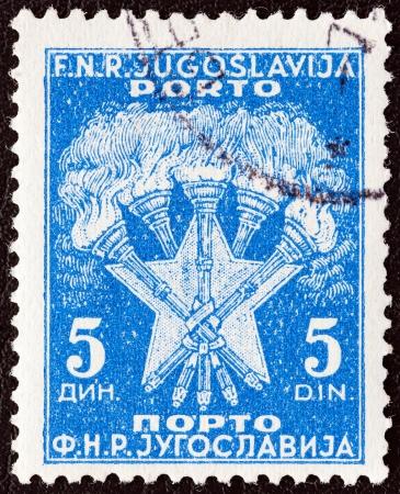 yugoslavia: YUGOSLAVIA - CIRCA 1952: A stamp printed in Yugoslavia shows 5 Torches and Star, the Coat of Arms of Yugoslavia, circa 1952.  Editorial