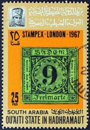 stempeln: QUAITI STATE IN THE HADHRAMAUT - CIRCA 1967: A stamp printed in Yemen from the STAMPEX - London Exhibition. Philatelic errors issue shows Baden, color error (1851), circa 1967.