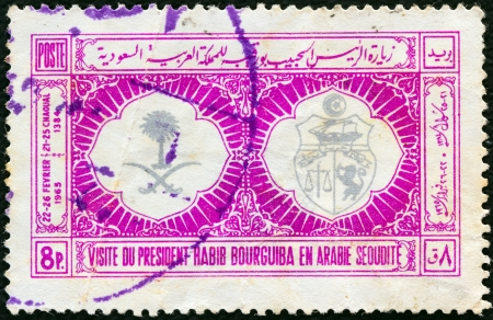 SAUDI ARABIA - CIRCA 1965: A stamp printed in Saudi Arabia issued for the visit of President Habib Bourguiba of Tunisia shows Arms of Saudi Arabia and Tunisia, circa 1965.
