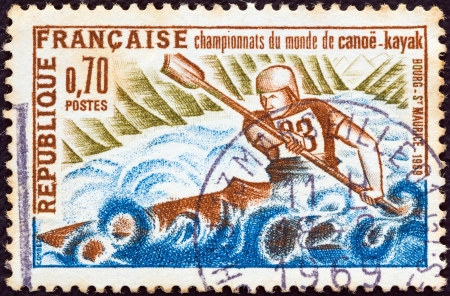 FRANCE - CIRCA 1969: A stamp printed in France issued for the International Canoe and Kayak Championships Bourg-Saint-Maurice , Savoy shows Kayak on Isere River, circa 1969.