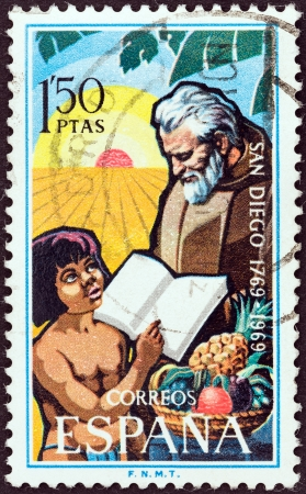 SPAIN - CIRCA 1969: A stamp printed in Spain issued for the bicentenary of San Diego, California shows Franciscan Friar and child, circa 1969.