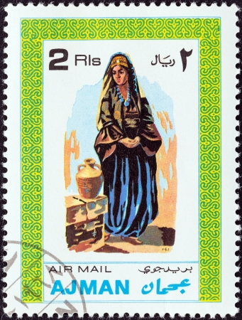 stempeln: AJMAN EMIRATE - CIRCA 1968  A stamp printed in United Arab Emirates from the  Men and Women in various garments  issue shows a woman in traditional costume, circa 1968