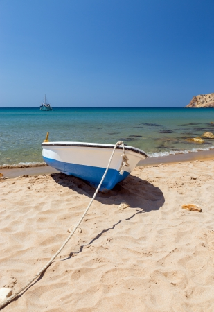 Summer seascape in a Greek island with a small boat on the beach photo