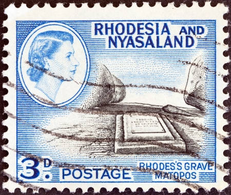 RHODESIA AND NYASALAND - CIRCA 1959  A stamp printed in Rhodesia shows Cecil John Rhodes grave, Matopos and Queen Elizabeth II, circa 1959