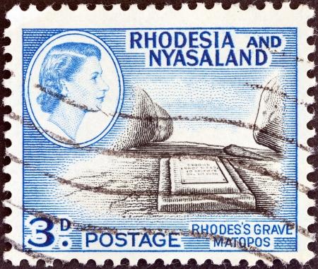 protectorate: RHODESIA AND NYASALAND - CIRCA 1959  A stamp printed in Rhodesia shows Cecil John Rhodes grave, Matopos and Queen Elizabeth II, circa 1959
