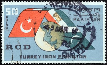 pacto: PAKIST�N - CIRCA 1965 Un sello impreso en Pakist�n expida por primera aniversario del Pacto Regional de Cooperaci�n para el Desarrollo muestra el globo y las banderas de Turqu�a, Ir�n y Pakist�n, alrededor de 1965 Editorial