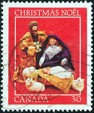 canada stamp: CANADA - CIRCA 1982  A stamp printed in Canada from the  Christmas  Nativity Scenes  issue shows Mary, Joseph and Baby Jesus, circa 1982   Editorial