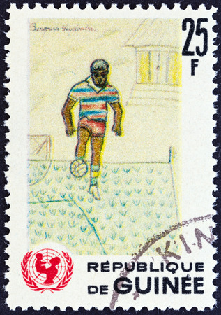 timbre: GUINEA - CIRCA 1966  A stamp printed in Guinea from the  The 20th Anniversary of UNICEF   issue shows footballer  children drawing , circa 1966  Editorial