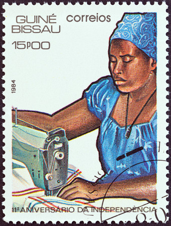 timbre: GUINEA-BISSAU - CIRCA 1984  A stamp printed in Guinea-Bissau from the  11th anniversary of Independence  issue shows woman sewing, circa 1984