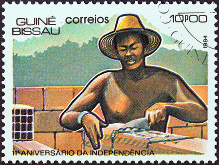 timbre: GUINEA-BISSAU - CIRCA 1984  A stamp printed in Guinea-Bissau from the  11th anniversary of Independence  issue shows laying bricks, circa 1984