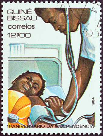 tending: GUINEA-BISSAU - CIRCA 1984  A stamp printed in Guinea-Bissau from the  11th anniversary of Independence  issue shows doctor tending child, circa 1984
