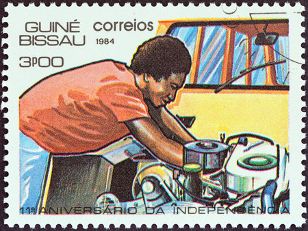GUINEA-BISSAU - CIRCA 1984  A stamp printed in Guinea-Bissau from the  11th anniversary of Independence  issue shows mechanic working on engine, circa 1984