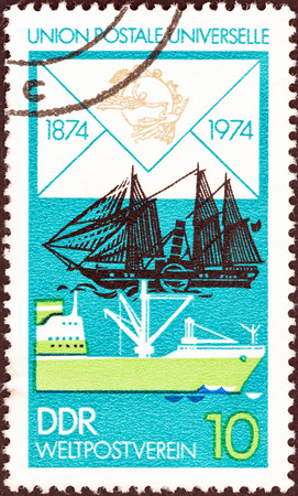 upu: GERMAN DEMOCRATIC REPUBLIC - CIRCA 1974  A stamp printed in Germany from the  Centenary of U P U  issue shows James Watt  paddle steamer  and Modern Freighter, circa 1974   Editorial