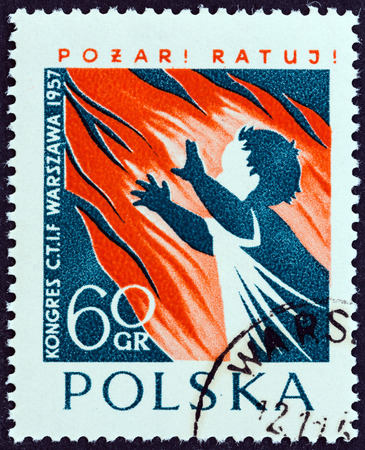 enveloping: POLAND - CIRCA 1957  A stamp printed in Poland issued for the International Fire Brigades Conference, Warsaw shows flames enveloping child, circa 1957