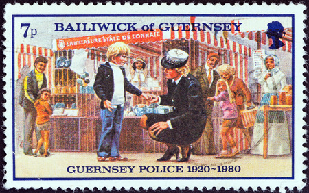 bailiwick: GUERNSEY - CIRCA 1980  A stamp printed in United Kingdom from the  60th Anniversary of Guernsey Police Force  issue shows policewoman with lost child, circa 1980   Editorial