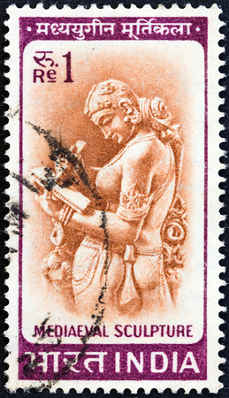 indian postal stamp: INDIA - CIRCA 1965  A stamp printed in India shows woman writing a letter  medieval sculpture , circa 1965   Editorial