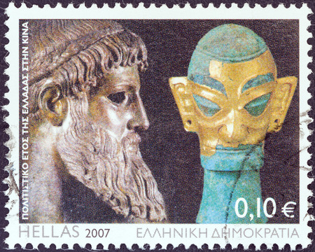 chinese postage stamp: GREECE - CIRCA 2007  A stamp printed in Greece issued for the Cultural Year of Greece in China shows Zeus of Artemision statue and bronze head sculpture with golden mask, Shang dynasty, circa 2007