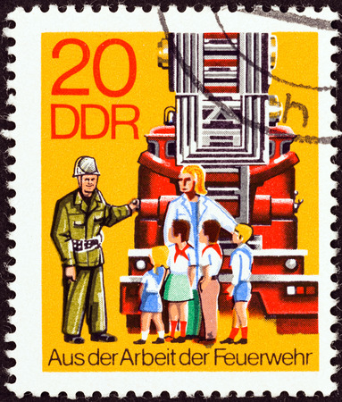 antique fire truck: GERMAN DEMOCRATIC REPUBLIC - CIRCA 1977: A stamp printed in Germany from the \Fire Brigade \ issue shows children visiting fire brigade, circa 1977.