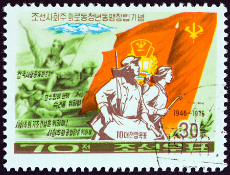 marchers: NORTH KOREA - CIRCA 1976: A stamp printed in North Korea from the 30th anniversary of Korean League of Socialist Working Youth  issue shows Marchers with Flags, circa 1976.