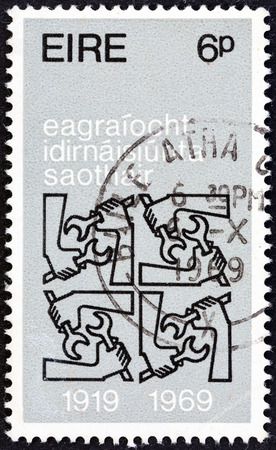 stempel: IRELAND - CIRCA 1969: A stamp printed in Ireland issued for the 50th anniversary of International Labor Organization shows Quadruple I.L.O. Emblems, circa 1969. Editorial