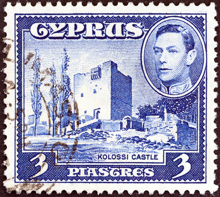 kypros: CYPRUS - CIRCA 1938: A stamp printed in Cyprus shows Kolossi Castle and King George VI, circa 1938.