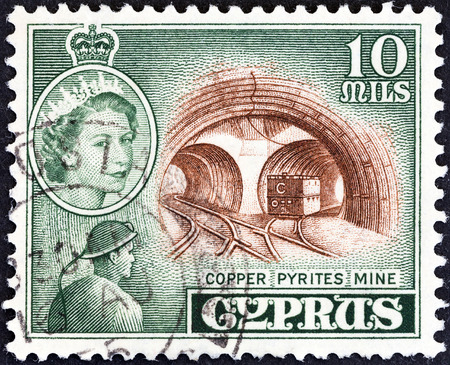 kypros: CYPRUS - CIRCA 1955: A stamp printed in Cyprus shows Mavrovouni Copper Pyrites Mine and Queen Elizabeth II, circa 1955.