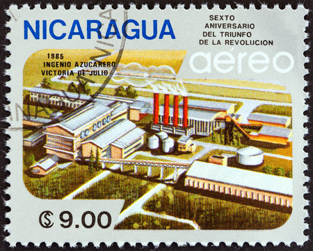 stempel: NICARAGUA - CIRCA 1985: A stamp printed in Nicaragua issued for the 6th anniversary of Revolution shows Victoria de Julio Sugar Factory, circa 1985.