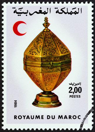 octogonal: MARRUECOS - CIRCA 1984: Un sello impreso en Marruecos muestra la Media Luna Roja y el recipiente de lat�n Octogonal, alrededor de 1984.