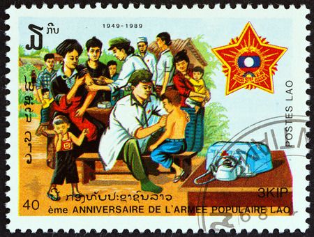 sello: LAOS - CIRCA 1989: A stamp printed in Laos from the 40th anniversary of Peoples Army  issue shows Army medics vaccinating civilians, circa 1989.
