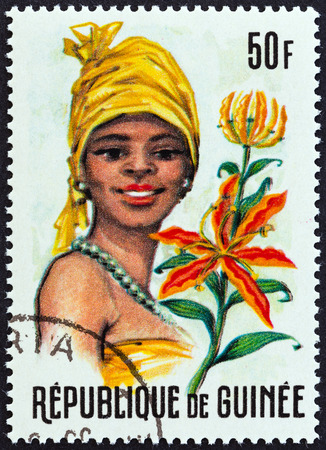 headdresses: GUINEA - CIRCA 1966: A stamp printed in Guinea from the \\\\\\\Guinean Flora and Female Headdresses \\\\\\\ issue shows Ammocharis and Woman, circa 1966.