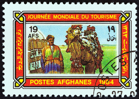 camel post: AFGHANISTAN - CIRCA 1984: A stamp printed in Afghanistan from the World Tourism Day  issue shows camel driver and camel, circa 1984.