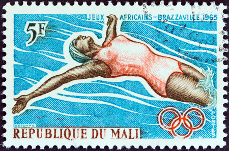 backstroke: MALI - CIRCA 1965: A stamp printed in Mali from the \\\1st African Games, Brazzaville\\\ issue shows backstroke swimmer, circa 1965.
