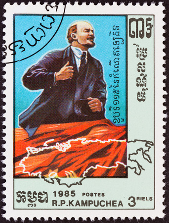 kampuchea: KAMPUCHEA - CIRCA 1985: A stamp printed in Kampuchea from the 115th birth anniversary of Lenin  issue shows Lenin on balcony and map, circa 1985. Editorial