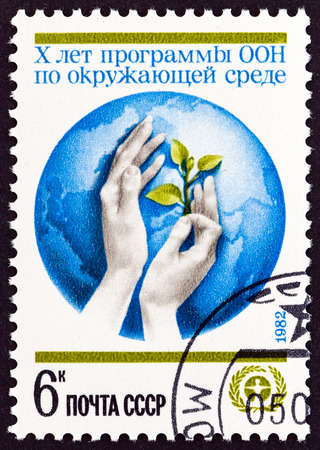 un used: USSR - CIRCA 1982: A stamp printed in USSR issued for the 10th anniversary of U.N. Environment Program shows Globe and hands holding Seedling, circa 1982. Editorial