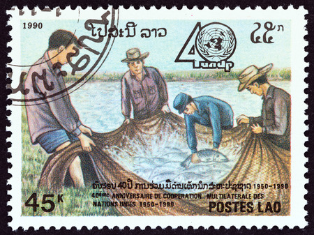un used: LAOS - CIRCA 1990: A stamp printed in Laos from the 40th Anniversary of United Nations Development Program  issue shows Fishermen and their catch, circa 1990.