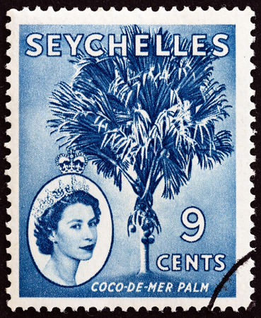 indian postal stamp: SEYCHELLES - CIRCA 1954: A stamp printed in Seychelles shows Coco-de-mer palm (Lodoicea maldivica) and Queen Elizabeth II, circa 1954. Editorial