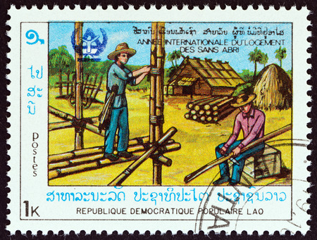 estampilla: LAOS  CIRCA 1987: A stamp printed in Laos from the International Year of Shelter for the Homeless  issue shows building bamboo house circa 1987. Editorial