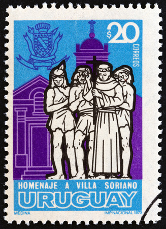 commemoration: URUGUAY  CIRCA 1973: A stamp printed in Uruguay issued for the commemoration of Villa Soriano the first Spanish settlement in Uruguay shows Priest Indians and Soriano Church circa 1973.