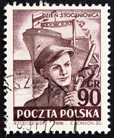 freighter: POLAND - CIRCA 1952: A stamp printed in Poland from the Shipbuilders Day  issue shows Brygada Makowskiego freighter under construction, circa 1952.