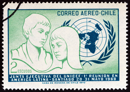 un used: CHILE - CIRCA 1971: A stamp printed in Chile issued for the 1st Latin-American Meeting of UNICEF Executive Council, Santiago 1969 shows Young People and U.N. Emblem, circa 1971.
