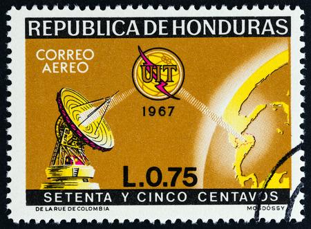 sello: HONDURAS - CIRCA 1968: A stamp printed in Honduras from the 100th Anniversary International Telecommunications Union  issue shows dish aerial, globe and I.T.U. emblem as satellite, circa 1968. Editorial