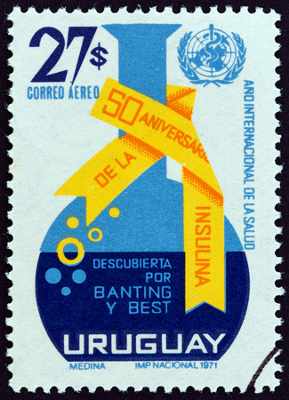 retort: URUGUAY - CIRCA 1972: A stamp printed in Uruguay issued for the 50th anniversary of the discovery of insulin by Frederick G. Banting and Charles H. Best shows Retort and WHO Emblem, circa 1972. Editorial