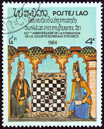 estampilla: LAOS - CIRCA 1984: A stamp printed in Laos from the 60th Anniversary of World Chess Federation  issue shows Two women playing illustration from King Alfonso Xs Book of Chess, circa 1984.